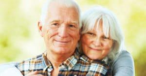 Senior couple smiling into camera
