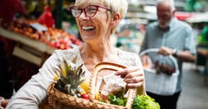 Senior woman at the market with basket of foos
